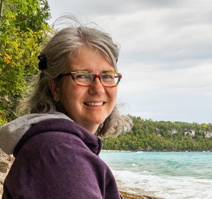 Mireille Messier devant un lac.